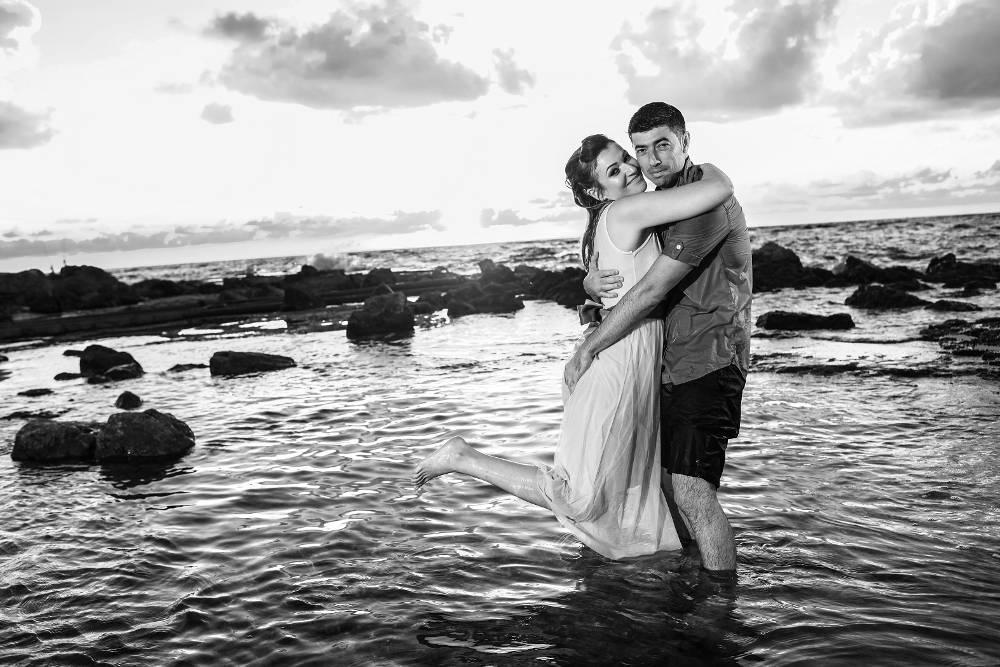 חתן וכלה בשחור לבן מתחבקים בחוף הים - trash the dress לדוגמה