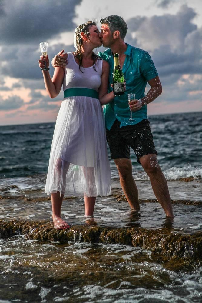 חתן וכלה עם שמפניה בחוף הים - trash the dress לדוגמה
