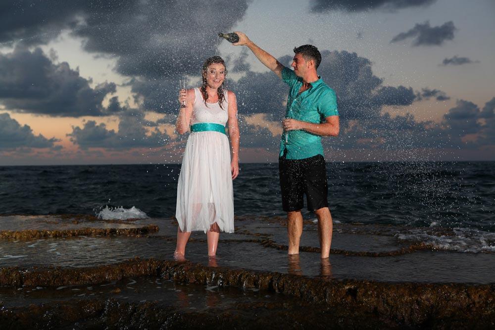 חתן וכלה עם שמפניה וקצף בחוף הים - trash the dress לדוגמה